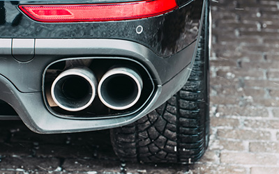 Close up of a car dual exhaust pipe parking lights, brake lights and wheel tires