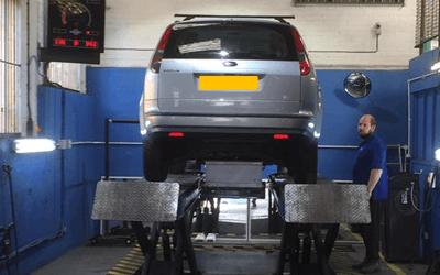 MOT test in garage with car on ramp in blue garage