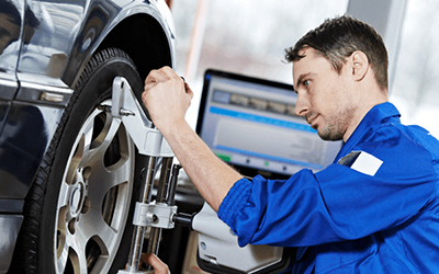 Man in blue overalls working on car tyre