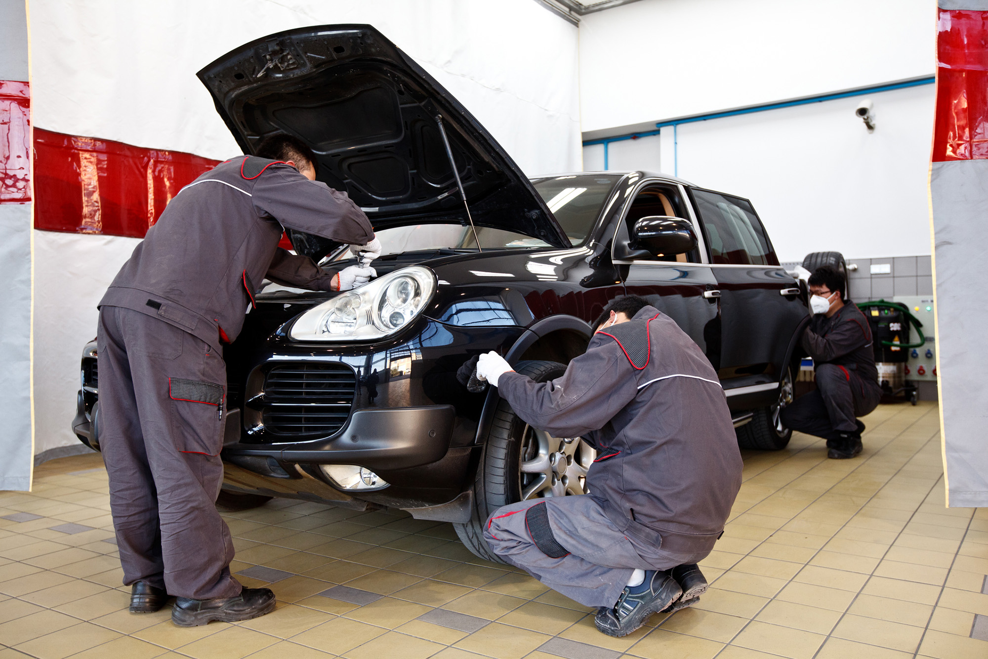 3 men working on Black Porsche jeep