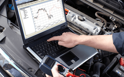 Car mechanic working on computer testing cars diagnostics